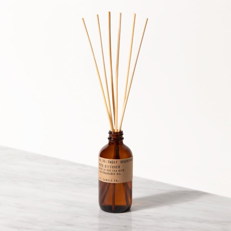 PF Candle Co Sweet Grapefruit classic line reed diffuser in a glass bottle with kraft label with rattan reed sticks inside