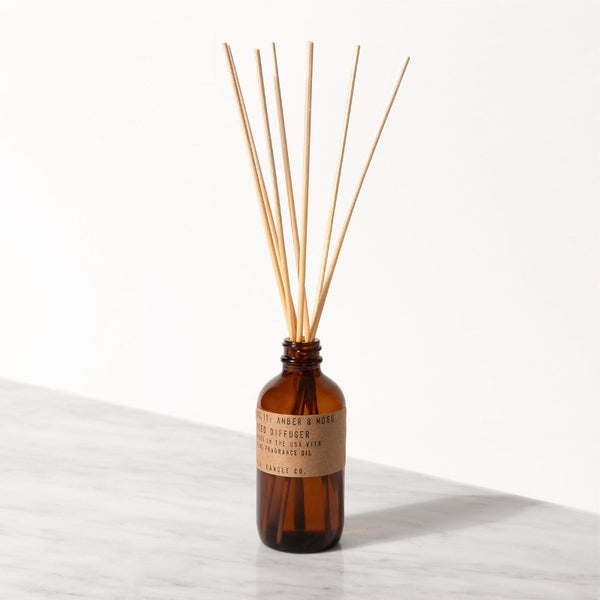 PF Candle Co Amber and Moss classic line reed diffuser in a glass bottle with kraft label with rattan reed sticks inside
