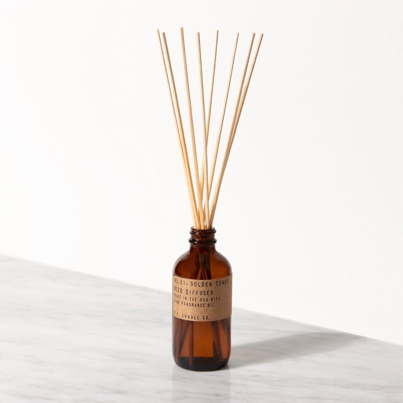 P.F. Candle Co. Golden Coast Reed Diffusers come in apothecary-inspired amber glass bottles with our signature kraft label and rattan reeds