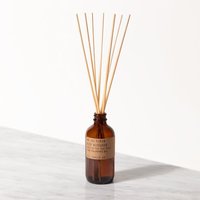 PF Candle Co Pinon classic line reed diffuser in a glass bottle with kraft label with rattan reed sticks inside