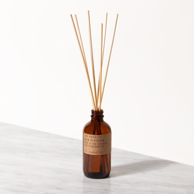 PF Candle Co Los Angeles classic line reed diffuser in a glass bottle with kraft label with rattan reed sticks inside
