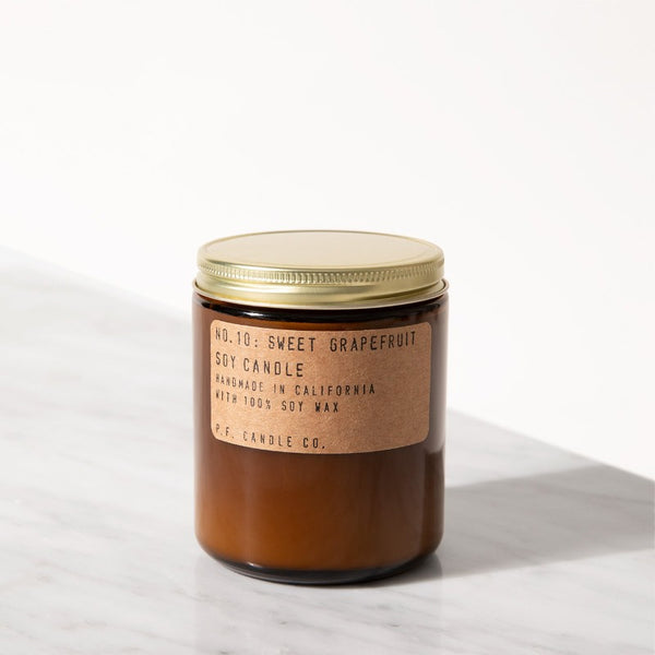 P.F. Candle Co. Sweet Grapefruit standard scented soy wax candle hand-poured into apothecary inspired amber jars with our signature kraft label and a brass lid