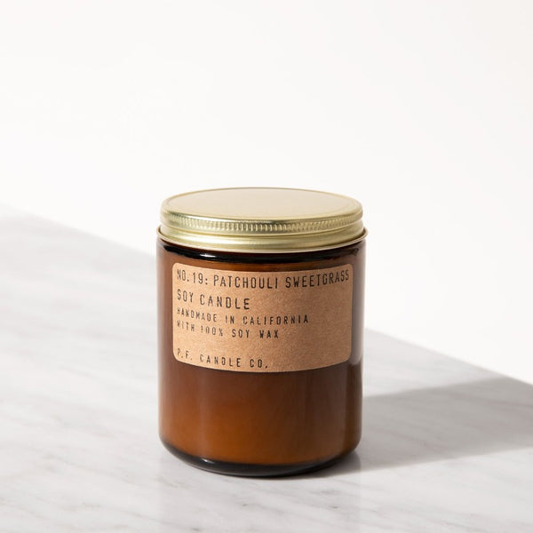 P.F. Candle Co. Patchouli Sweetgrass standard scented soy wax candle hand-poured into apothecary inspired amber jars with our signature kraft label and a brass lid