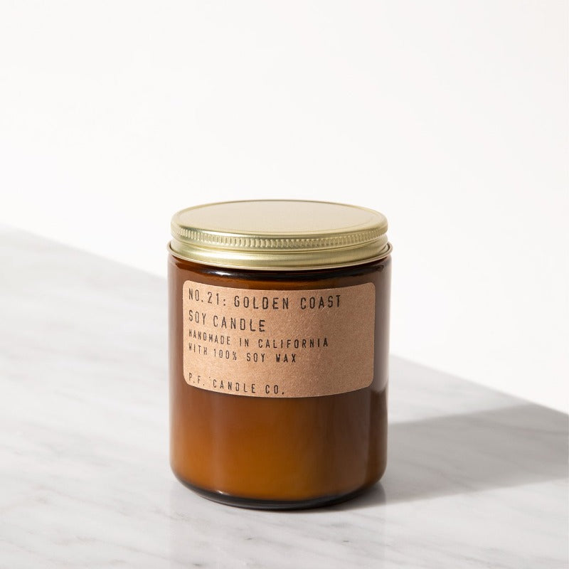 P.F. Candle Co. Golden Coast standard scented soy candle hand-poured into apothecary inspired amber jars with our signature kraft label and a brass lid