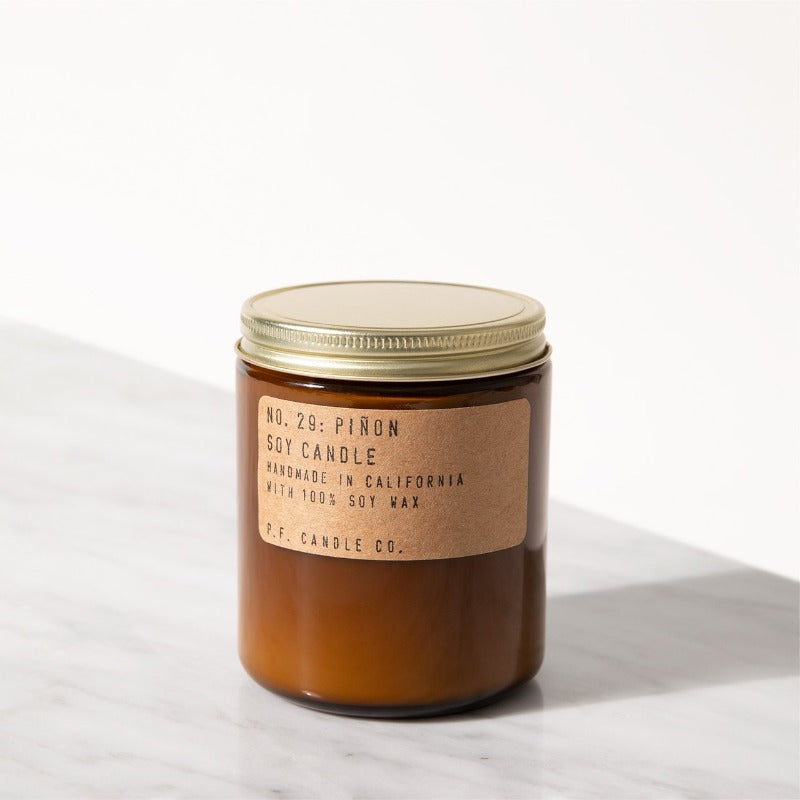 P.F. Candle Co. Pinon standard scented soy wax candle hand-poured into apothecary inspired amber jars with our signature kraft label and a brass lid