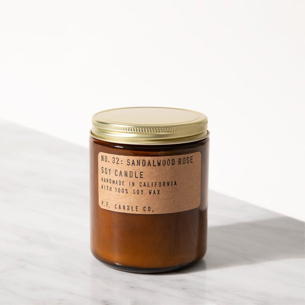 P.F. Candle Co. Sandalwood Rose standard scented soy wax candle hand-poured into apothecary inspired amber jars with our signature kraft label and a brass lid