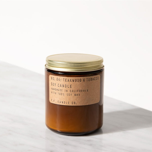 P.F. Candle Co. Teakwood & Tobacco standard scented soy wax candle hand-poured into apothecary inspired amber jars with our signature kraft label and a brass lid