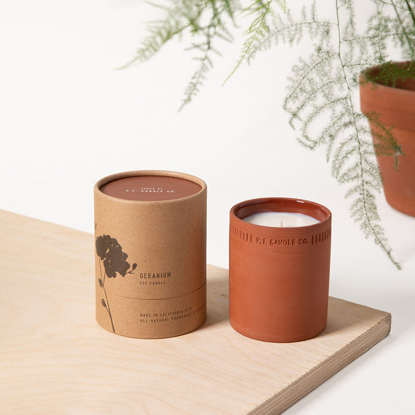PF Candle Co Geranium standard terra candle next to the packaging with a fern in the back