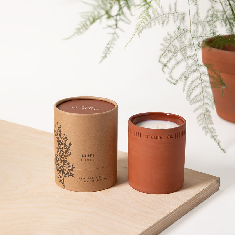 PF Candle Co Juniper standard terra candle next to the packaging with a fern in the back