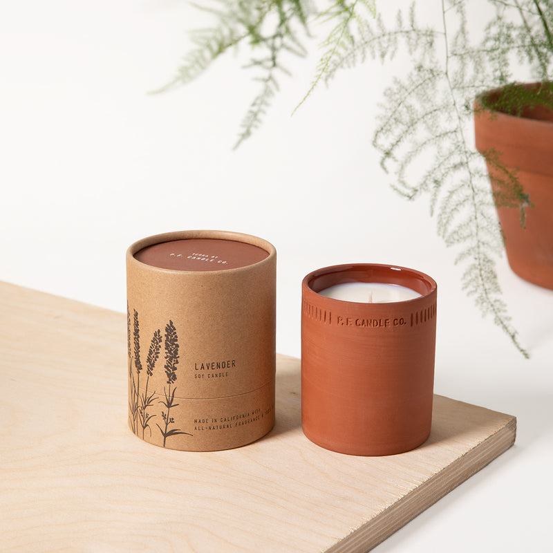 PF Candle Co Lavender standard terra candle next to the packaging with a fern in the back