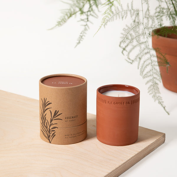 PF Candle Co Rosemary standard terra candle next to the packaging with a fern in the back