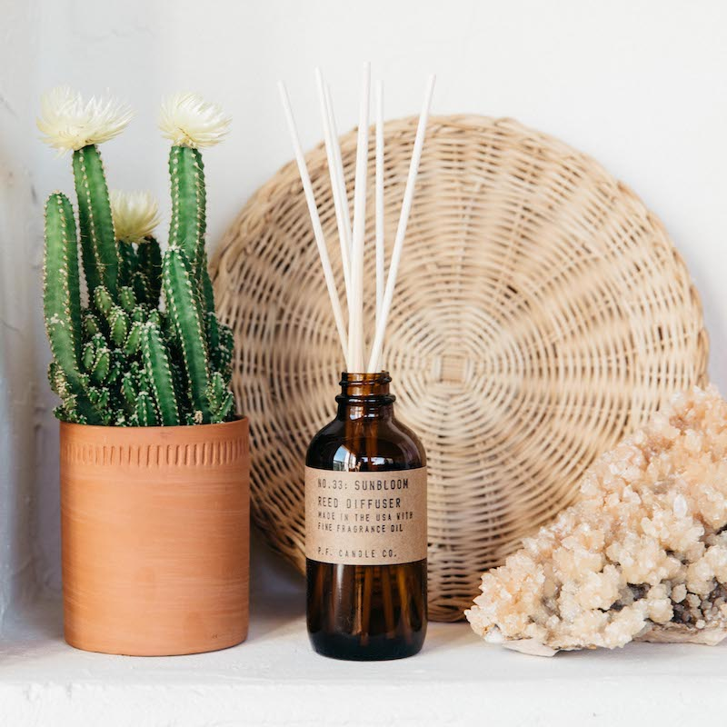PF Candle Co Sunbloom reed diffuser between a potted cactus and crystal, with a wicker basket in the background.