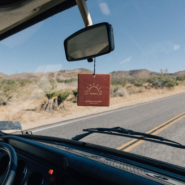 P.F. Candle Co. Teakwood and Tobacco car fragrance hanging from rearview mirror in front of desert road