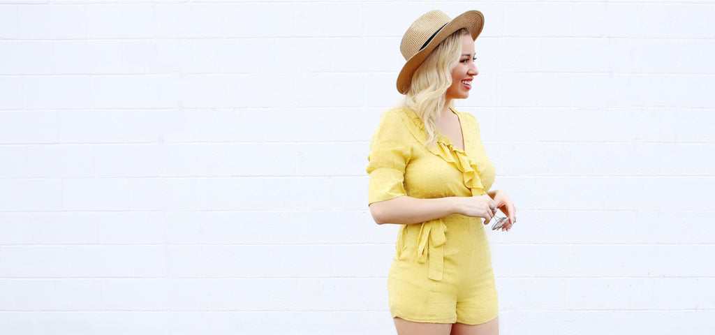 Lacey wear a bright yellow romper and sun hat