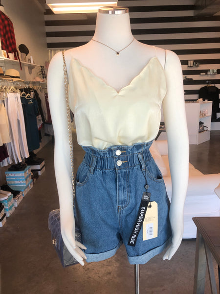 Mannequin wearing a buttercream cami and high waisted denim shorts