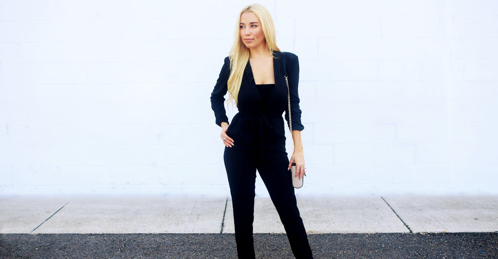 Model wearing a black long sleeve tuxedo jumpsuit against white wall