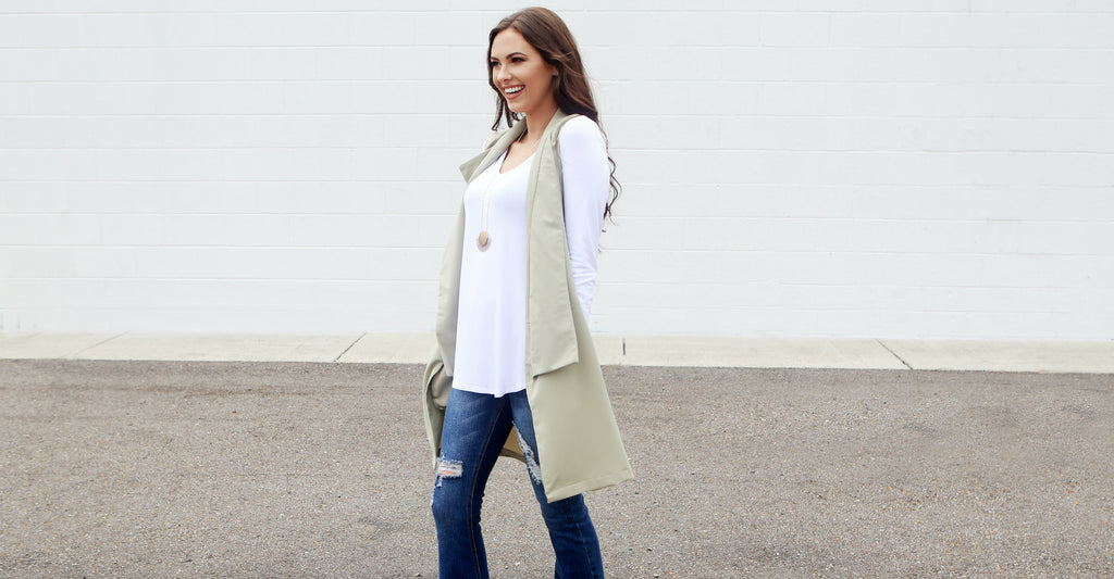 Kristine wearing a basic white tee with moss green vest and flare jeans