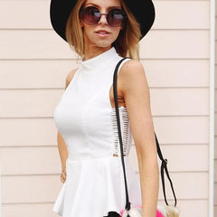 Model is wearing white peplum top and round sunglasses and black hat