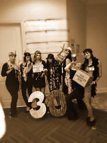Seven women dressed up in 20's flapper costumes
