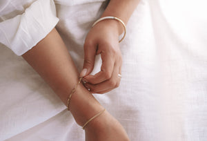 hammered brass and inset bone and horn bangle bracelet worn on woman's hands