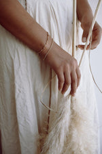 beaded bracelet set fair trade modeled on woman holding pampas grass