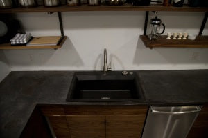 Custom walnut kitchen cabinets with steel shelves and concrete countertops
