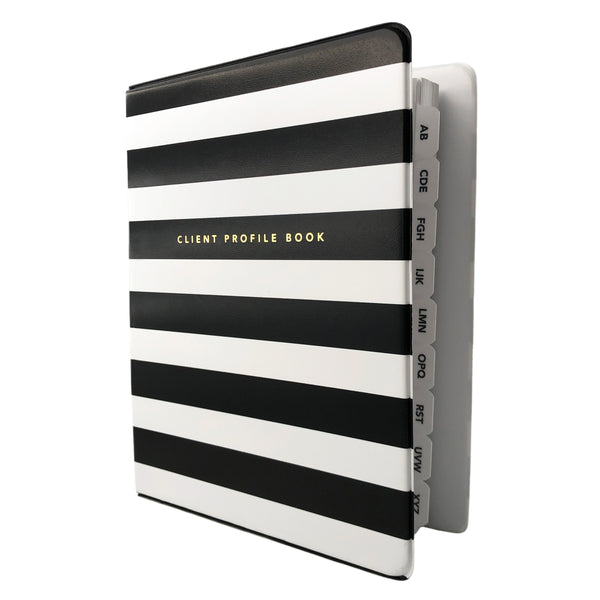 Angled view of black and white striped salon client profile book. Alpha divider tabs peeking out.