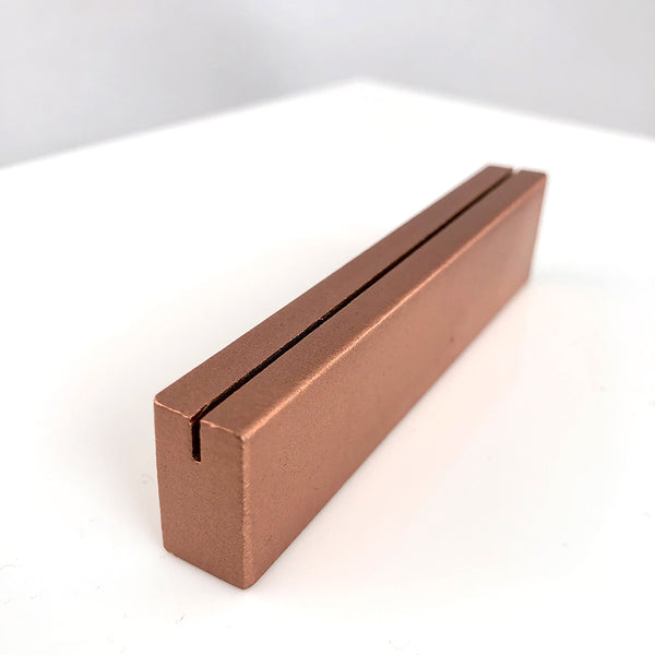 Angled view of copper metal tabletop sign stand