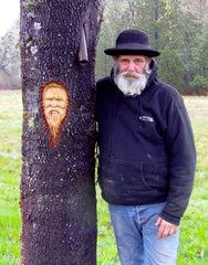 A dear friend mushroom harvester beside his image carved into a tree by a fellow forager friend.