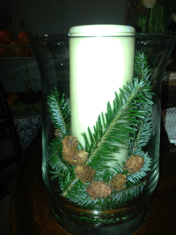 candles with pine cone in vase