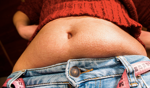 Woman with protruding belly over waistband