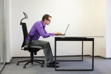 Man at Desk hunched over laptop