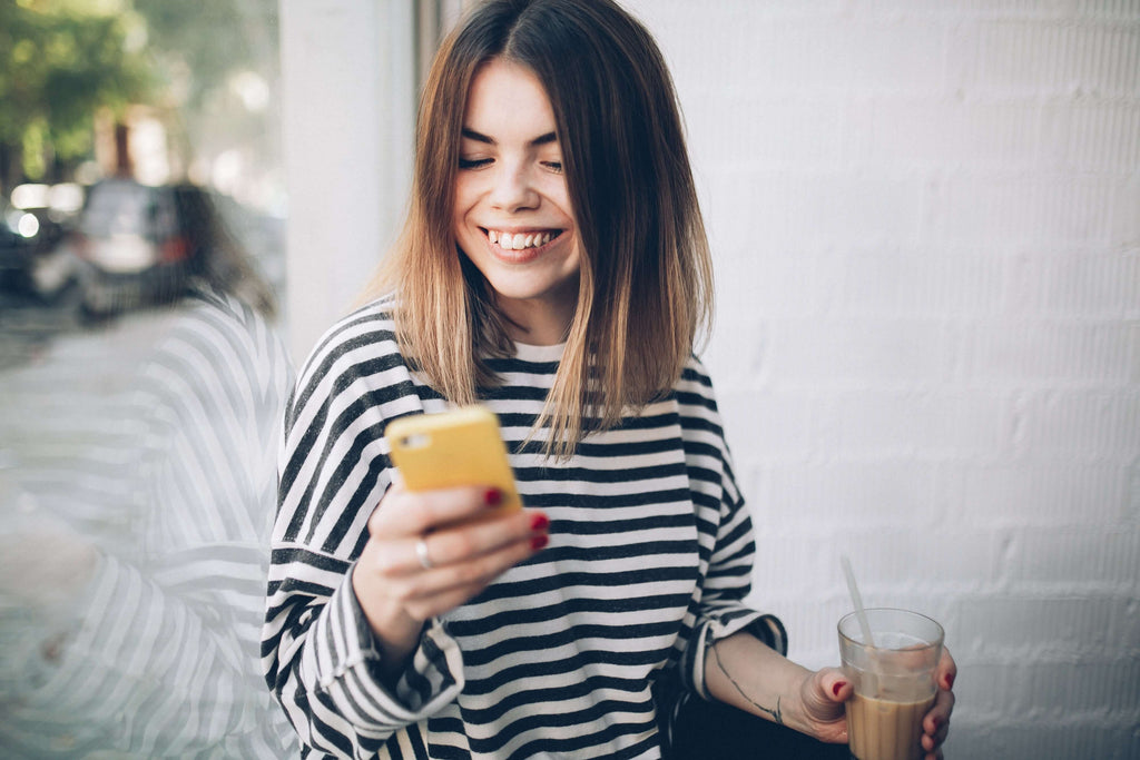 Woman in a striped shirt, holding and looking down at her phone while smiling. On her other hand, she has a glass with a drink and straw.