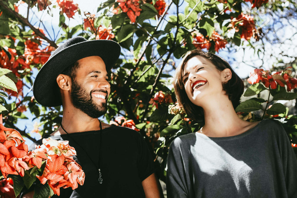 a bearded man in a hat and a woman laughing in front of a tree with pink flowers