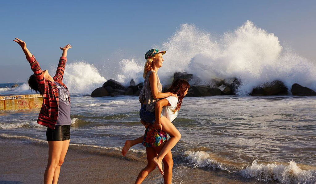 Three women, standing near the shore while enjoying the sea waves. The girl wearing a white shirt is carrying on her back a blonde girl who is wearing a cap and, the other girl on their back is raising her hand while looking at the sky