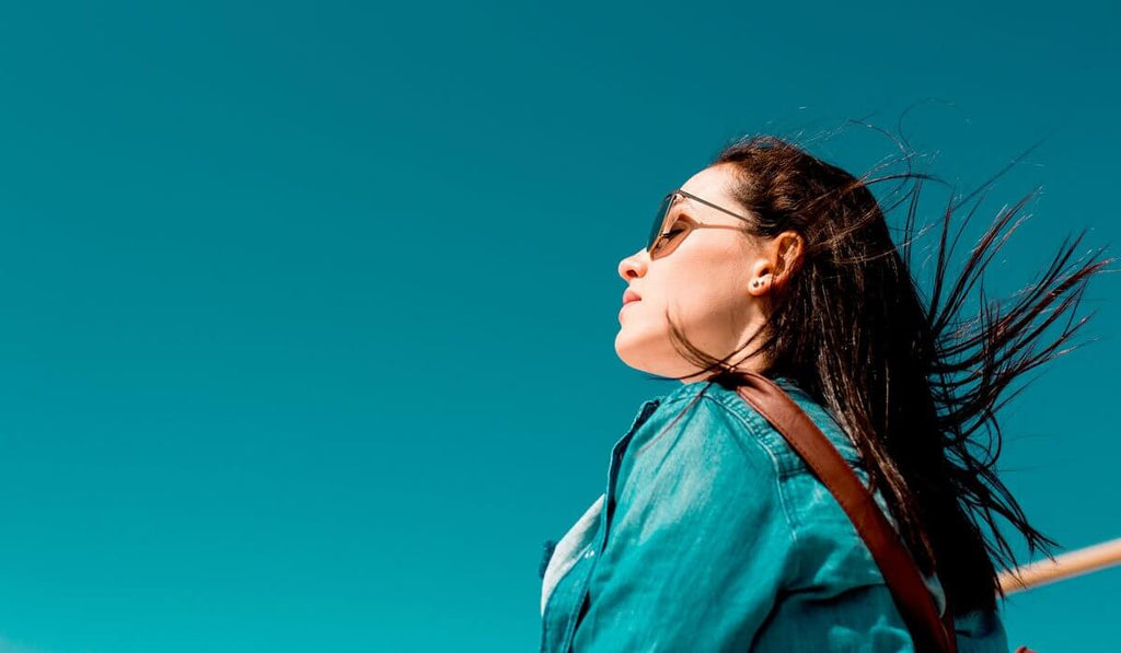Woman wearing sunglasses while closing her eyes and looking at the sky.