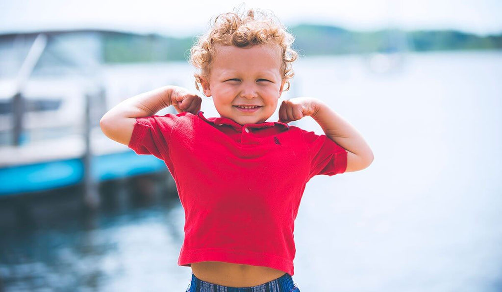 A blonde little boy wearing a red polo shirt with curly hair smiling and posing like a bodybuilder behind him is a boat in the lake