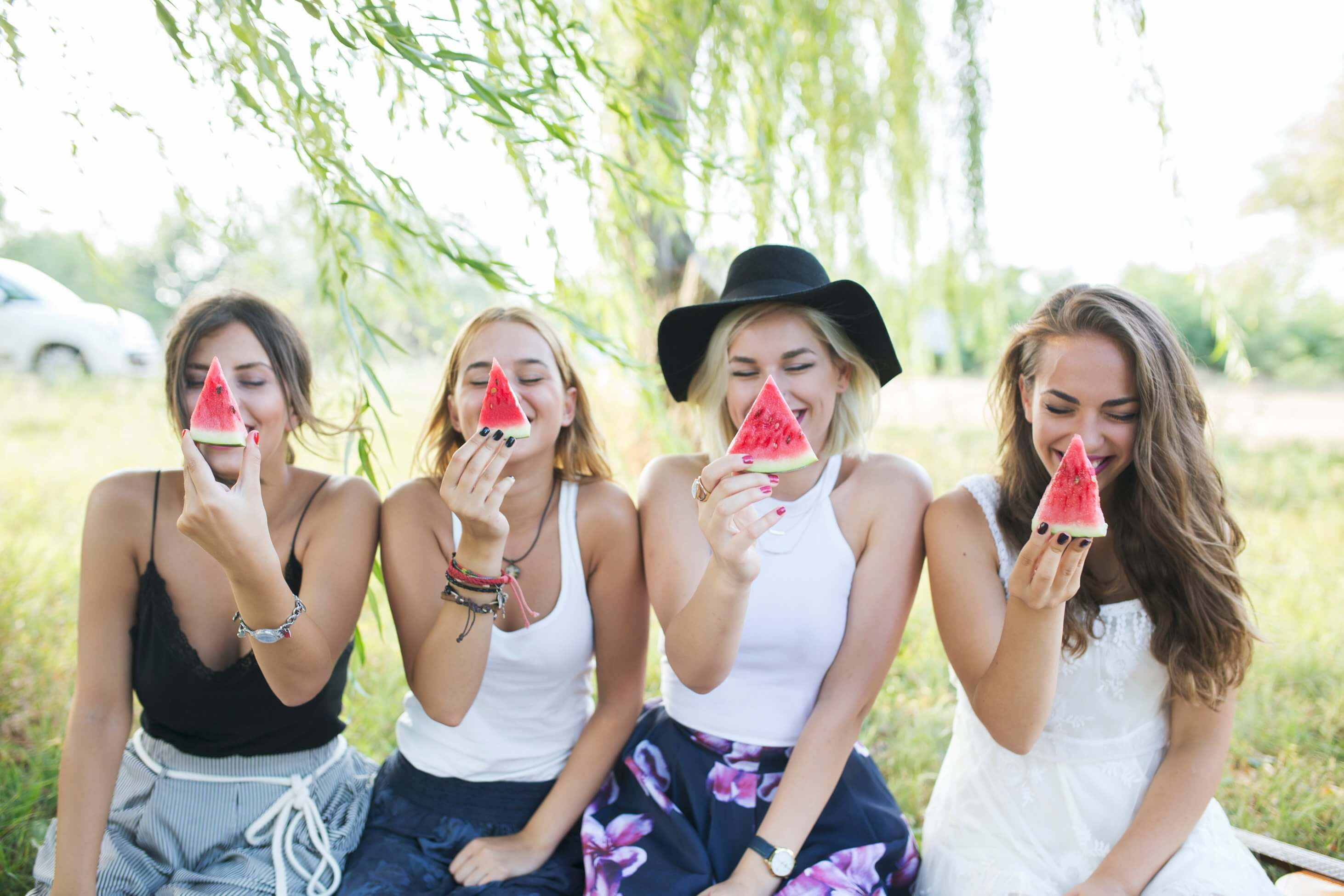 Four girls closing their eyes and smiling while holding a cut of watermelon while sitting on the grass