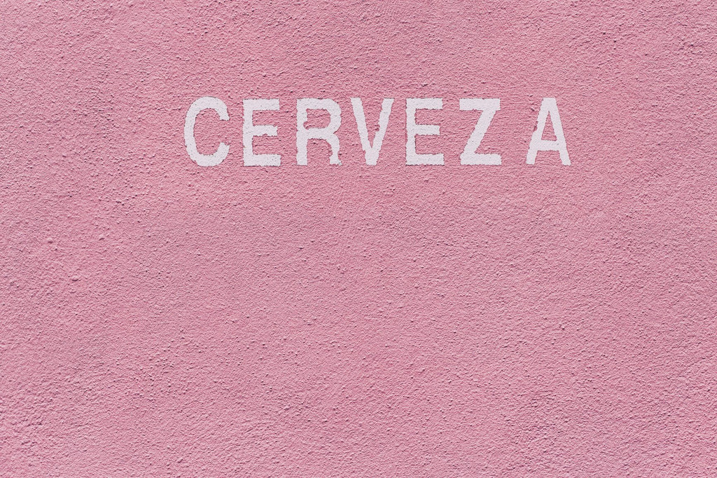 "A Pink wall with a painted text ""CERVEZA"""
