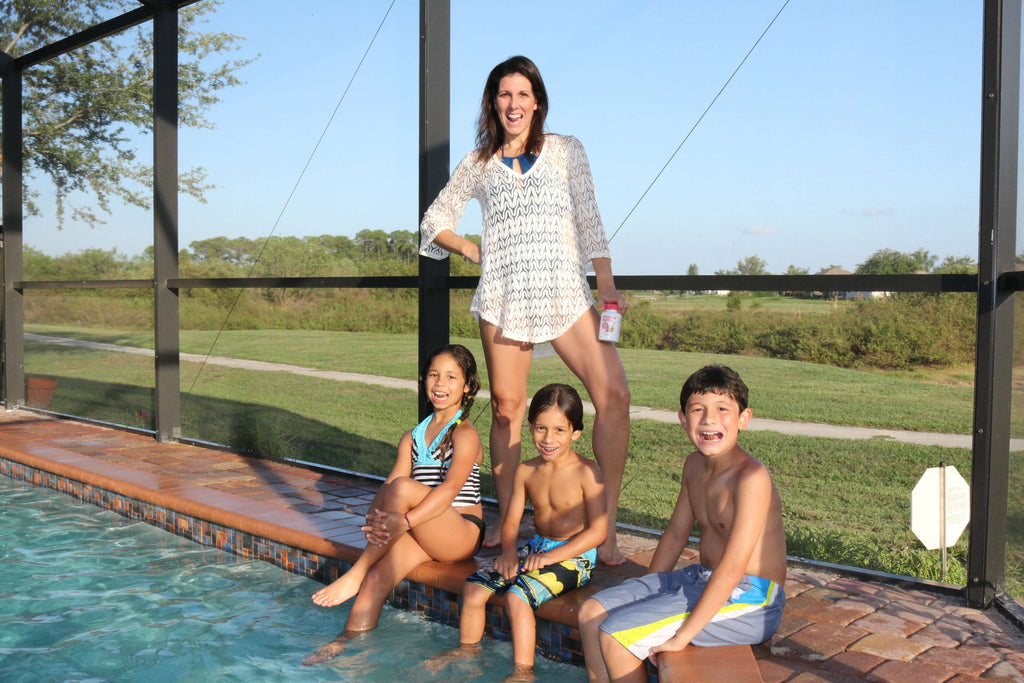 A mother standing and her three kids smiling while sitting in the swimming pool
