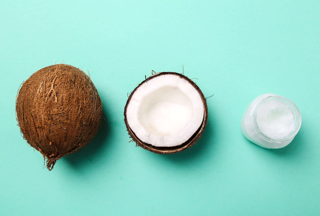 Whole coconut, Half-cut coconut, and coconut oil in a jar with a bright cyan background