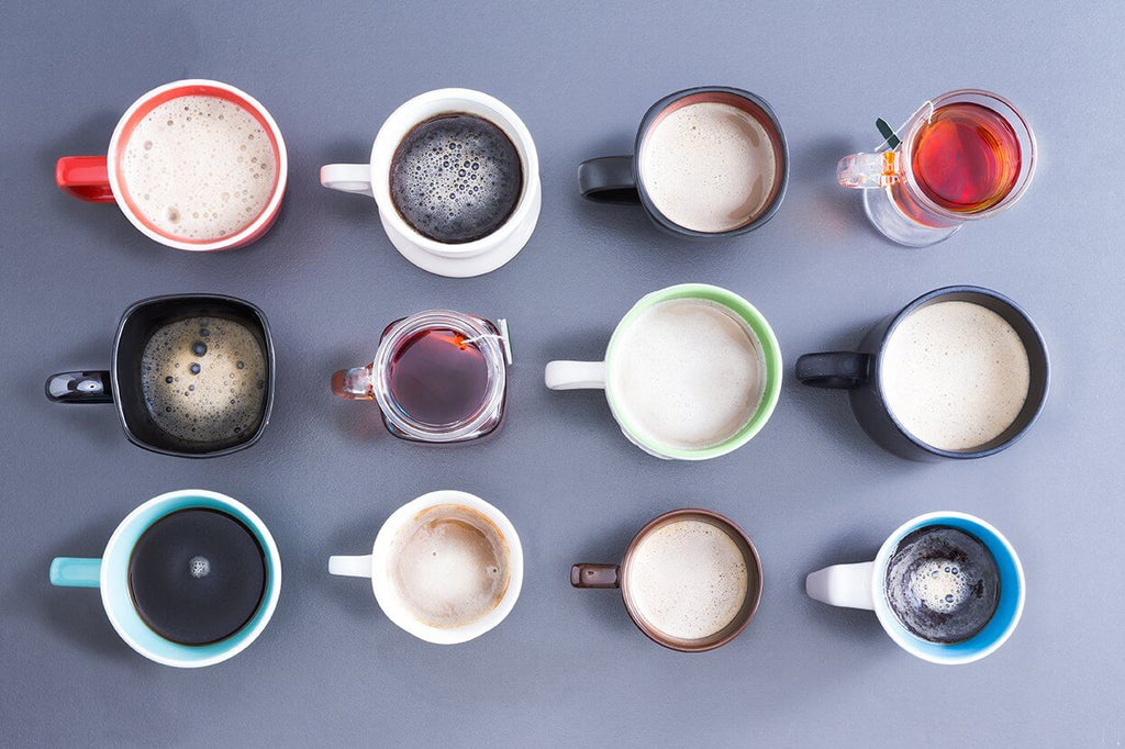 Different types of coffee in different sizes and colored mugs in a gray tabletop