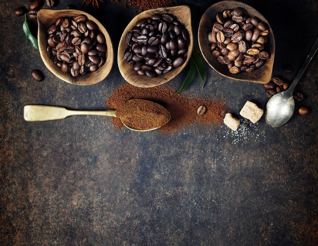 Different types of beans in a bowl and a ground coffee on a spoon in a black stain background