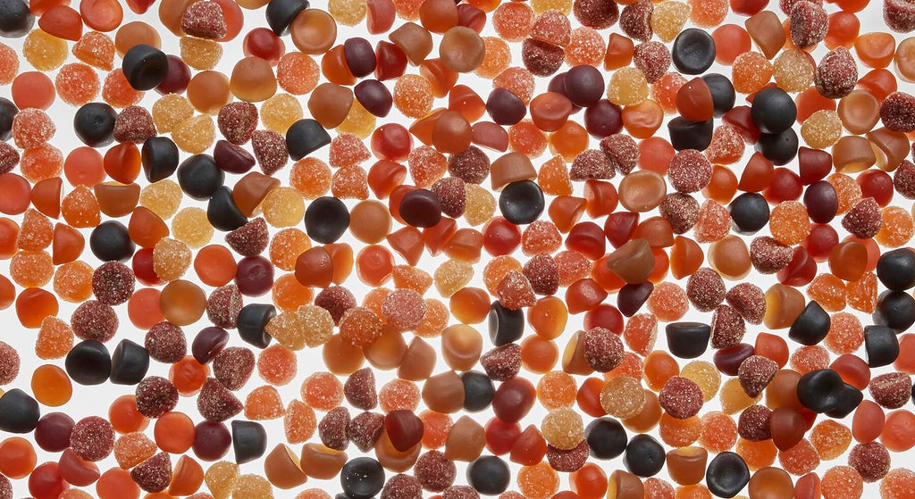 Multiple SmartyPants multivitamins gummies scattered with a different colors