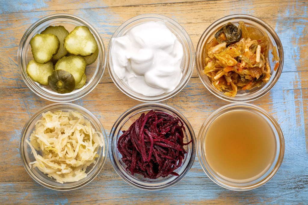 On a wooden table are six different types of ingredients in a bowl with probiotic content, pickles, yogurt, kimchi, kefir, sauerkraut, miso