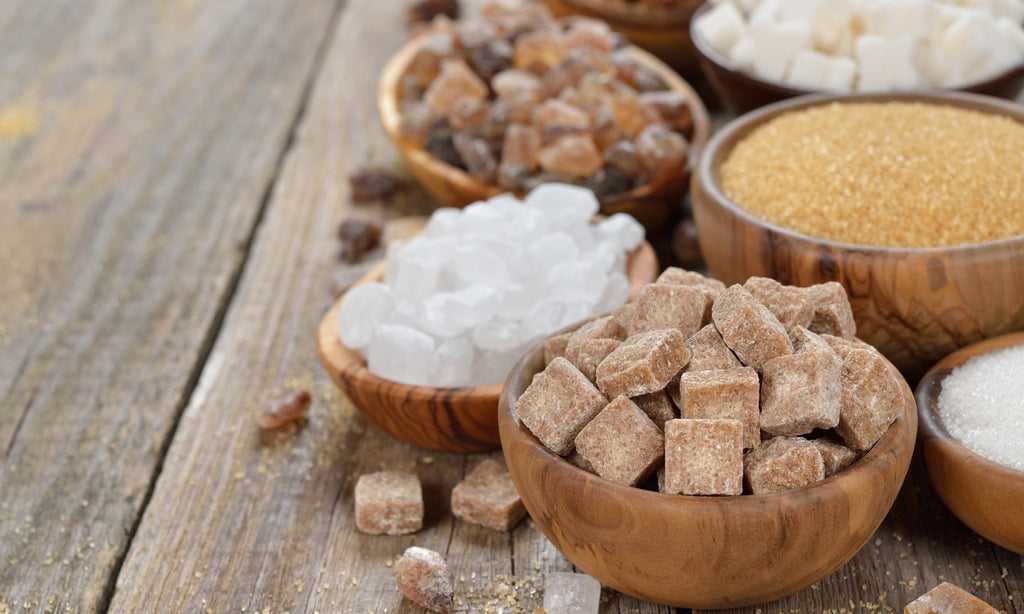 On a wooden table are different varieties of sugar in a bowl