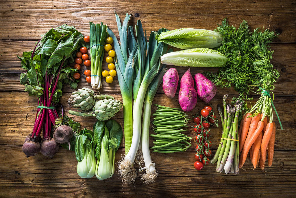 On a wooden table are different vegetables: onions, carrots, tomatoes, cabbage,  asparagus that arrange perfectly