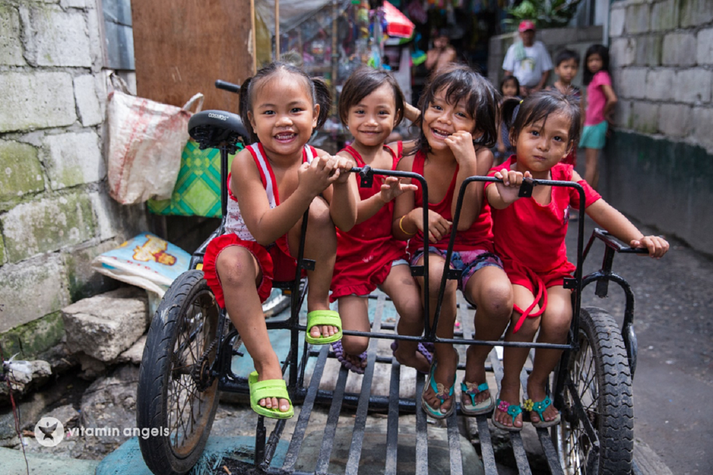 Four little girls wearing a red sleeveless shirt while smiling and riding in the sidecar of a bike