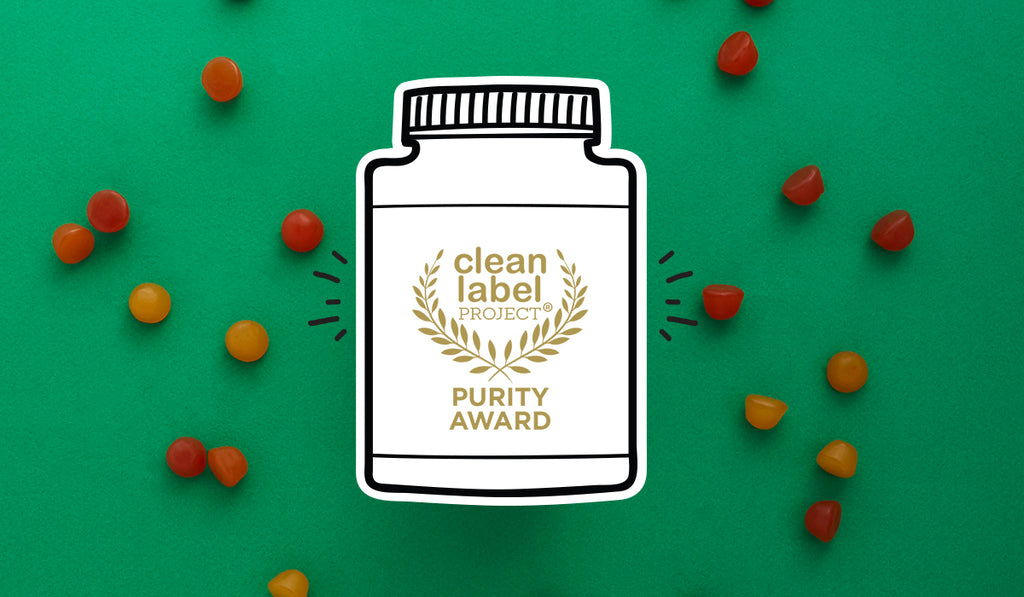 SmartyPants Purity Award from the Clean Label Project in a green background with scattered SmartyPants gummy vitamins