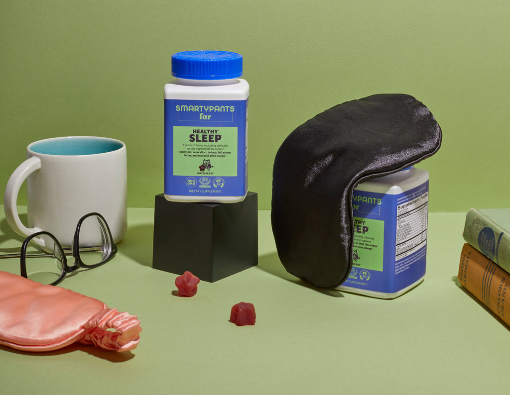 In a green backdrop is Smartypants for Healthy Sleep product, another product is being covered by a sleeping mask  on the side are some mug, reading glasses and books